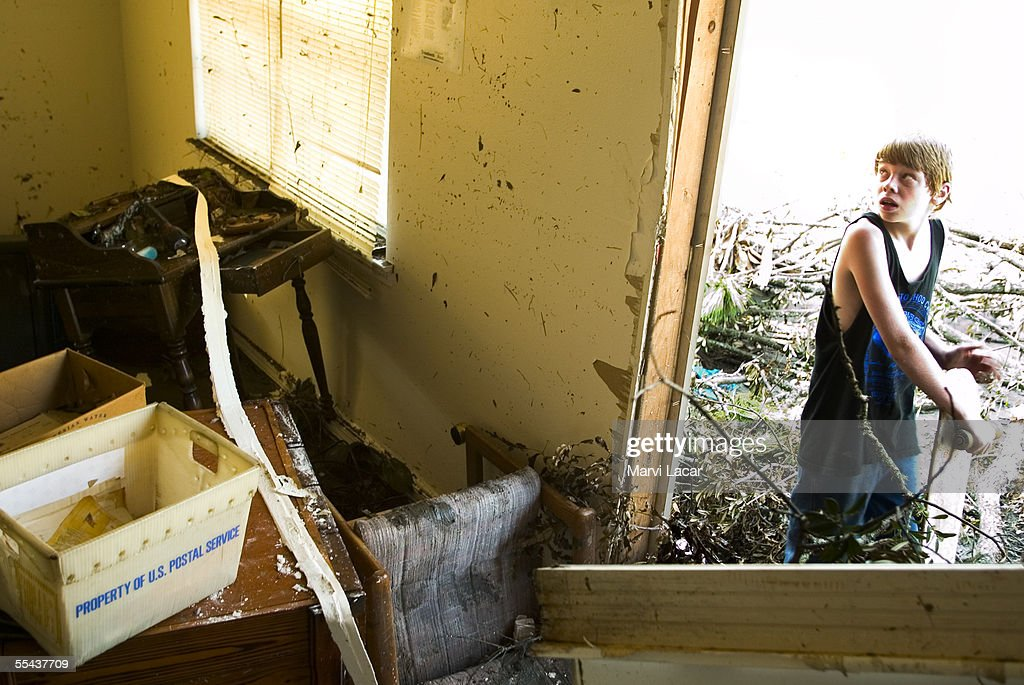 Jeffrey Phillips (14) examines the inside of his family's house on 441 Waveland Ave. on September 3, 2005 in Waveland, Mississippi. Hurricane Katrina's category 5 strength left the coast of Florida, Alabama, Mississippi and Louisina in ruins. Mississippi confirmed death toll was over 120 by Thursday as more rescue teams combed the devasted areas.