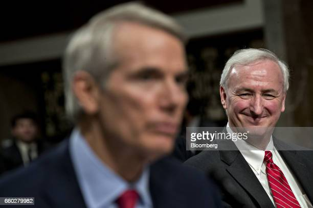 Jeffrey Rosen deputy transportation secretary nominee for US President Donald Trump right smiles while being introduced by Senator Rob Portman a...