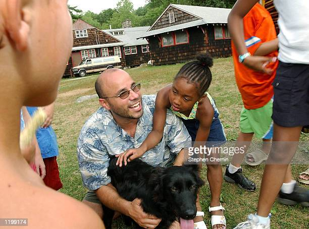 Jeffrey Rumpf regional coordinator of Catholic Youth Organization pets camp mascot Teddy next to campers participating in the CYO's 'Little Heroes'...