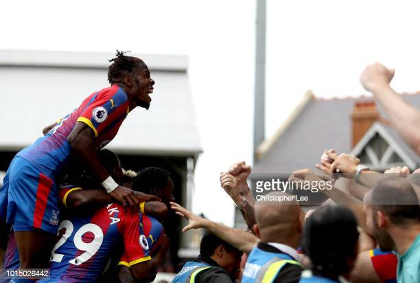 Jeffrey Schlupp of Crystal Palace celebrates with teammates after scoring his team's first goal during the Premier League match between Fulham FC and...