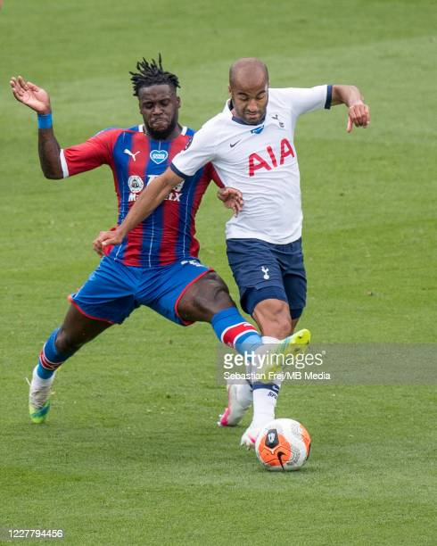 Jeffrey Schlupp of Crystal Palace competes for the ball with Lucas Moura of Tottenham Hotspur during the Premier League match between Crystal Palace...