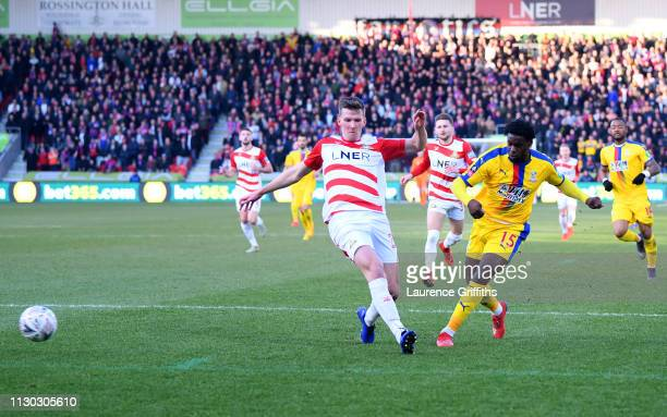 Jeffrey Schlupp of Crystal Palace shoots past Paul Downing of Doncaster Rovers as he scores his team's first goal during the FA Cup Fifth Round match...