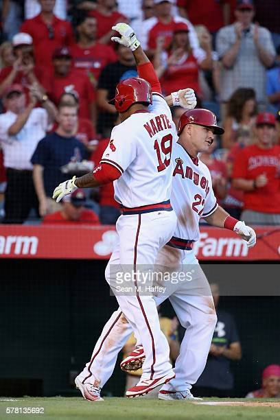 Jefry Marte is congratulated by Mike Trout of the Los Angeles Angels of Anaheim after hitting a threerun homerun during the first inning of a...