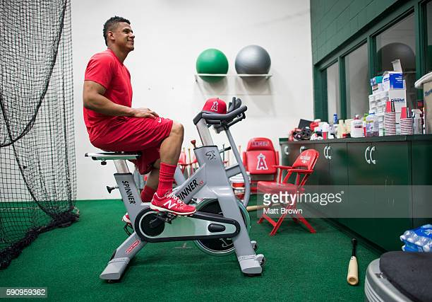 Jefry Marte of the Los Angeles Angels of Anaheim watches film while using a stationary bike in the clubhouse batting cage before the game against the...