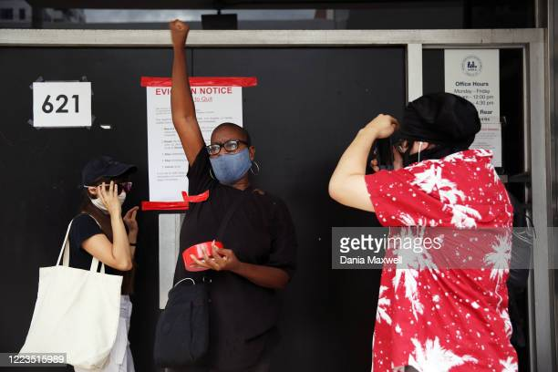 Jehan C., center, raises their fist after taping an eviction notice to the Apartment Association of Greater Los Angeles building during a march with...