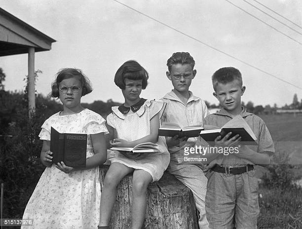 Jehovah's Witness children reading books outdoors
