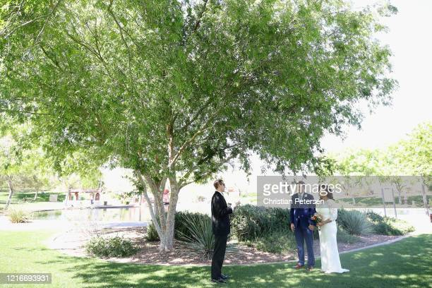 Jehovah's witness wedding between groom Daniel and bride Paloma is commenced outside for social distancing at Anthem Park on April 03 2020 in Anthem...
