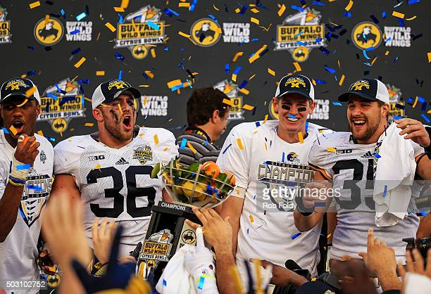 Jehu Chesson, Joe Kerridge, Joe Bolden and Jake Rudock of the Michigan Wolverines cheer after receiving the championship trophy after the Buffalo...