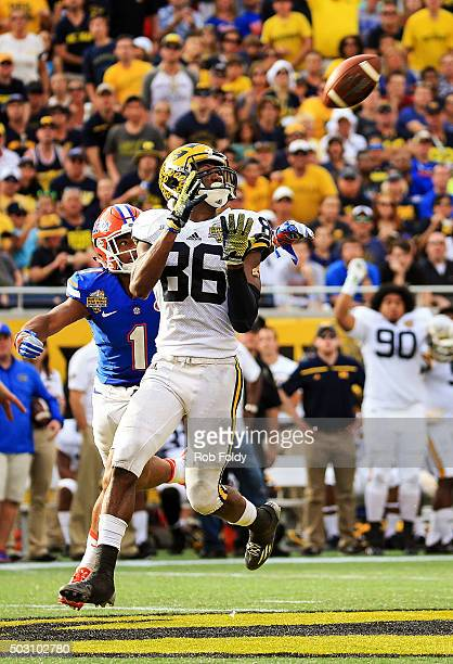 Jehu Chesson of the Michigan Wolverines catches a pass past Vernon Hargreaves III of the Florida Gators during the second half of the Buffalo Wild...