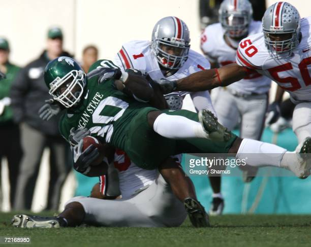 Jehuu Caulcrick of the Michigan State Spartans is tackled by Jay Richardson, Vernon Gholston and Marcus Freeman of the Ohio State Buckeys during...