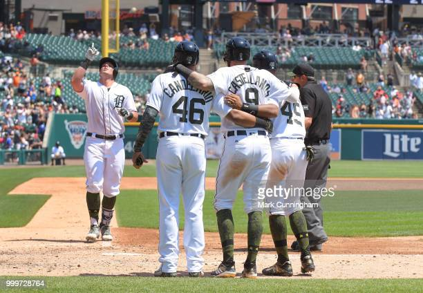 Jeimer Candelario Nicholas Castellanos and Dixon Machado of the Detroit Tigers wait at home plate to greet teammate James McCann after he hit a grand...