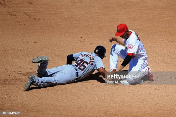 Jeimer Candelario of the Detroit Tigers dives back to second base as Andrelton Simmons of the Los Angeles Angels of Anaheim applys the tag in a pick...