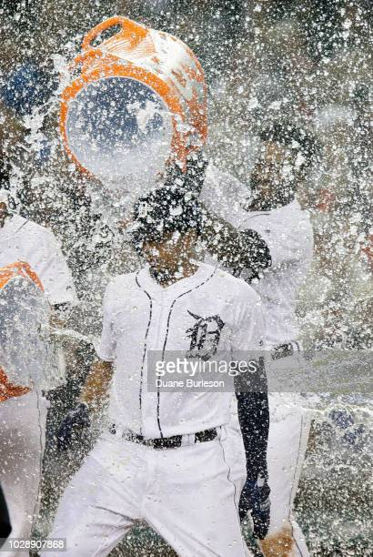 Jeimer Candelario of the Detroit Tigers has water dumped on him by Niko Goodrum after hitting a two run walkoff home run to defeat the St Louis...