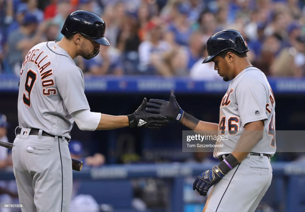 Jeimer Candelario #46 of the Detroit Tigers is congratulated by Nicholas Castellanos #9 after hitting a solo home run in the seventh inning during MLB game action against the Toronto Blue Jays at Rogers Centre on June 29, 2018 in Toronto, Canada.