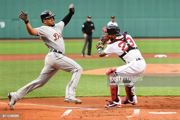 Jeimer Candelario of the Detroit Tigers is safe at home plate as he avoids the tag of Blake Swihart of the Boston Red Sox in the first inning of a...