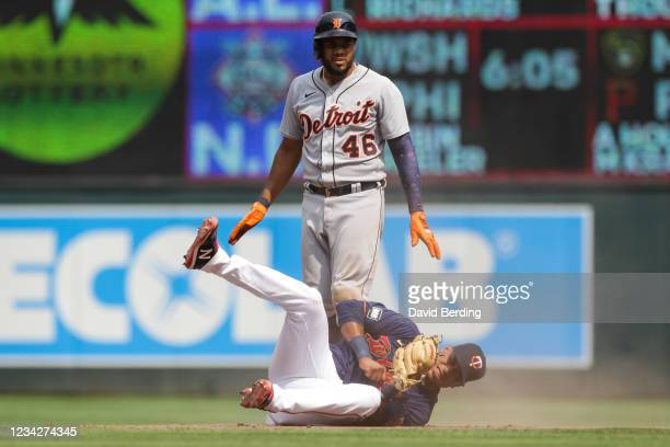 Jeimer Candelario of the Detroit Tigers looks on after hitting an RBI double while Jorge Polanco of the Minnesota Twins reacts after fielding the...