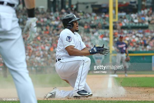 Jeimer Candelario of the Detroit Tigers scores on the sacrifice fly by Victor Martinez during the fifth inning of the game against the Minnesota...