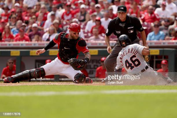 Jeimer Candelario of the Detroit Tigers slides into home plate to score a run past Tucker Barnhart of the Cincinnati Reds in the sixth inning at...