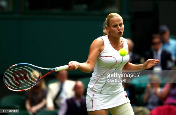 Jelena Dokic of Australia returns a shot during her first round match against Francesca Schiavone of Italy on Day One of the Wimbledon Lawn Tennis...