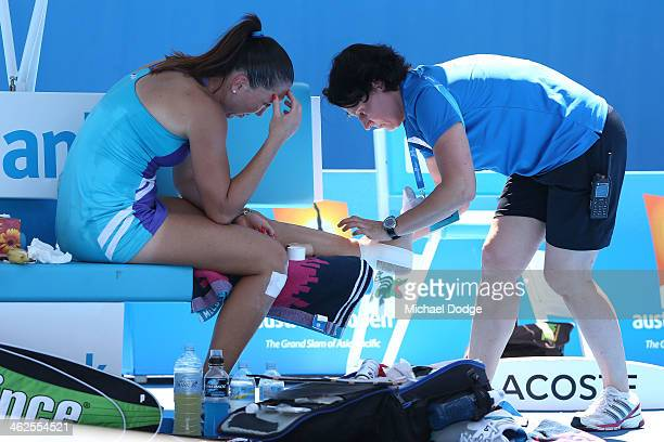Jelena Jankovic of Serbia receives treatment on her ankle in her first round match against Misaki Doi of Japan during day two of the 2014 Australian...