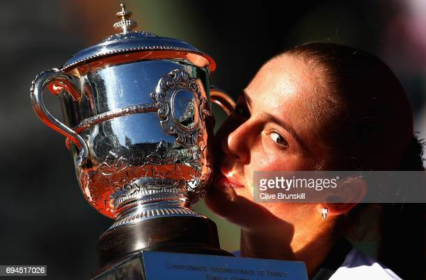 Jelena Ostapenko of Latvia celebrates victory by kissing the trophy following the ladies singles final match against Simona Halep of Romania on day...