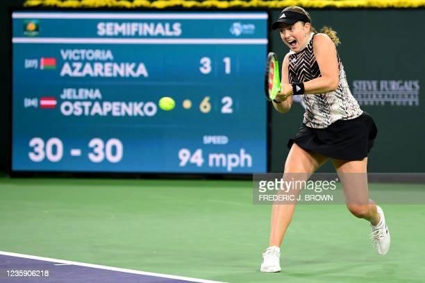 Jelena Ostapenko of Latvia hits a backhand return to Victoria Azarenka of Belarus during their semifinal match at the ATP-WTA Indian Wells tennis...