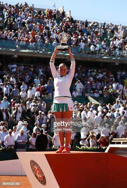 Jelena Ostapenko of Latvia lifts the Suzanne Lenglen Cup following her victory during the ladies singles final against Simona Halep of Romania on day...