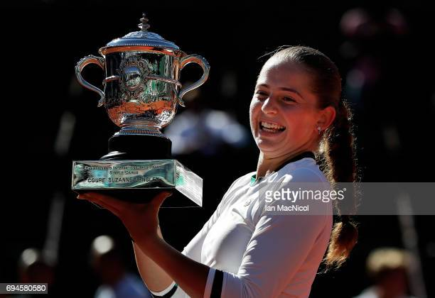 Jelena Ostapenko of Latvia poses with the trophy after her victory during her Women's Single Final match with Simona Halep of Romania on day fourteen...