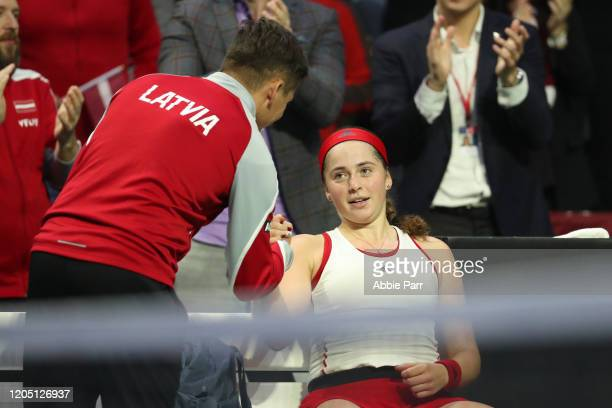 Jelena Ostapenko of Latvia shakes hands with Latvia Team Captain Adrians Zguns after defeating Sofia Kenin of USA in three sets during the 2020 Fed...
