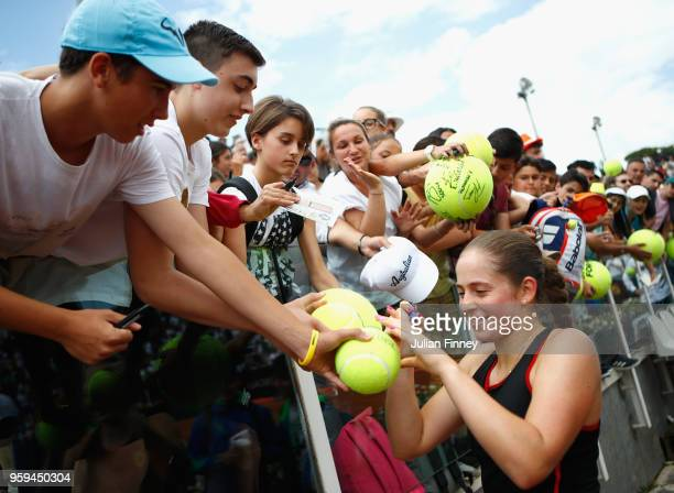 Jelena Ostapenko of Latvia signs autographs following victory in her singles match against Johanna Konta of Great Britain during day four of the...
