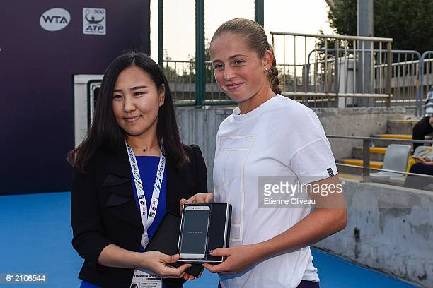 Jelena Ostapenko of Lithuania receives a gift during the LeMobile Clinic event on day three of the 2016 China Open at the National Tennis Centre on...