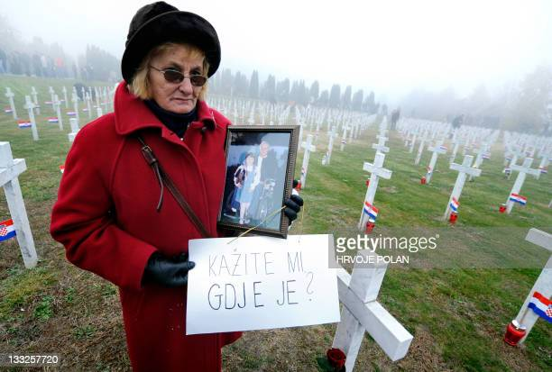 Jelena Radic shows a picture of her disappeared husband and war victim Mijo as she holds a sign reading Tell me where is he at the 1991 war victims...
