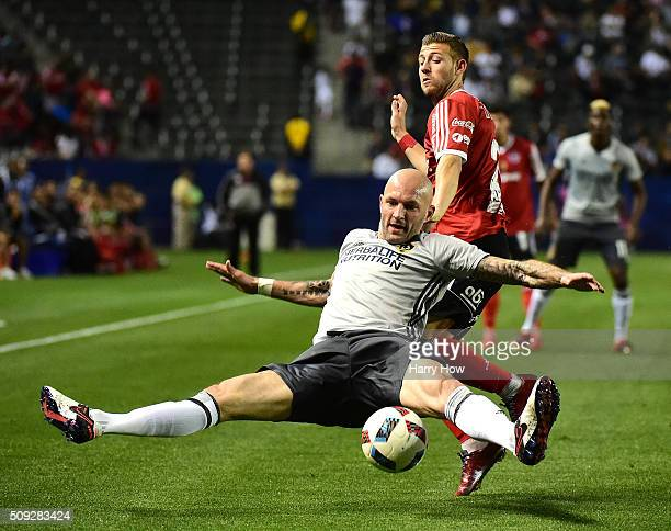 Jelle Van Damme of the Los Angeles Galaxy loses his footing as he defends against Paul Arriola of Club Tijuana during the first half at StubHub...