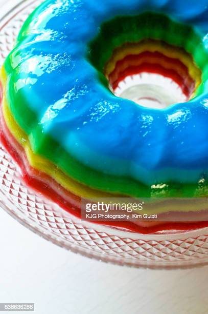 jello mold in rainbo color order on clear glass platter - gelatin dessert stock photos and pictures