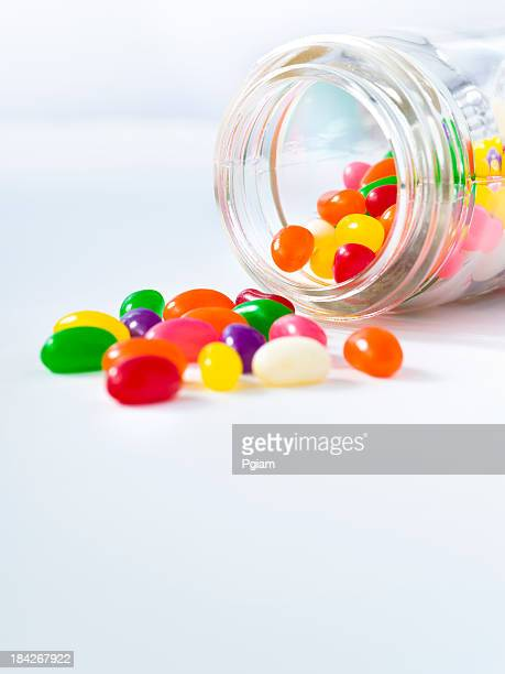 Jelly beans spill out of a jar