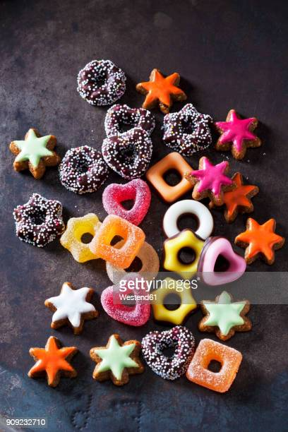 Jelly confectionery, coloured cinnamon stars and other Christmas cookies on dark ground