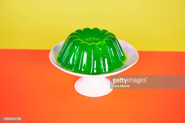jelly mould on cake stand with yellow and orange background - cakestand stock pictures, royalty-free photos & images