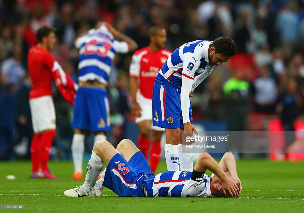 Jem Karacan of Reading consoles team mate Alex Pearce in defeat after the FA Cup Semi Final between Arsenal and Reading at Wembley Stadium on April 18, 2015 in London, England.