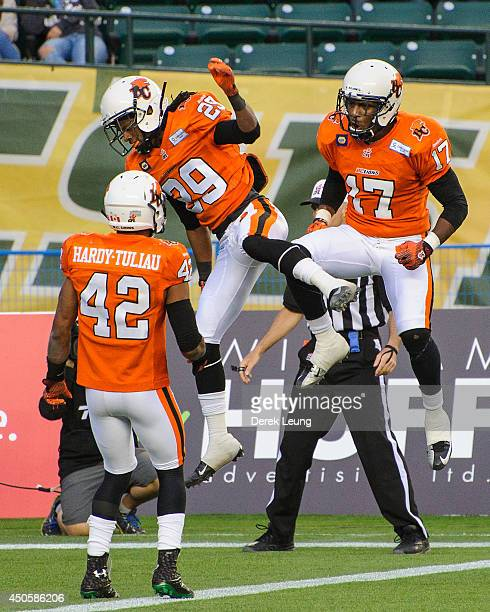Jemarlous Moten of the BC Lions celebrates along with teammates Thomas Spoletini and TJ Lee after stopping a pass by the Edmonton Eskimos during a...