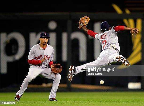Jemile Weeks of the Boston Red Sox leaps but misses a blooper hit by Alcides Escobar of the Kansas City Royals in shallow left field as Yoenis...