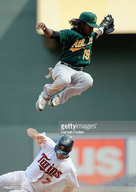 Jemile Weeks of the Oakland Athletics leaps over the sliding Joe Mauer of the Minnesota Twins on May 28 2012 at Target Field in Minneapolis Minnesota...