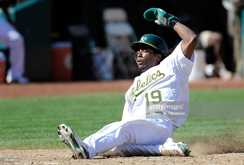 Jemile Weeks #19 of the Oakland Athletics slide in safe at home scoring on an RBI single by Coco Crisp #4 against the Texas Rangers in the eighth inning during an MLB baseball game at O.co Coliseum on September 22, 2011 in Oakland, California. The Ahtletics won the game 4-3.