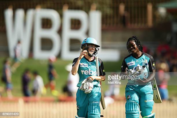 Jemma Barsby and Deandra Dottin of the Heat celebrate as they walk from the field after victory in the the Women's Big Bash League match between the...