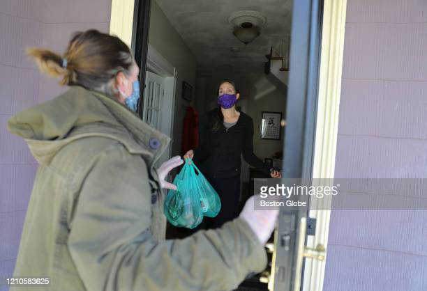 Jen Bullard right accepts a delivery from Roisin O'Rourke of The Dark Horse Public House in Somerville MA on April 19 2020 The Broadway establishment...