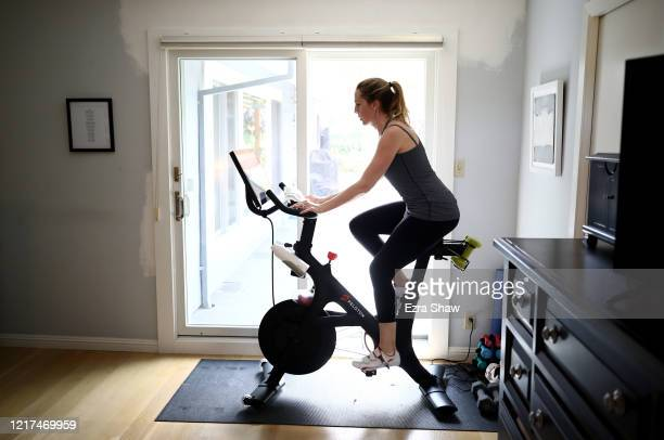 Jen Van Santvoord rides her Peloton exercise bike at her home on April 07, 2020 in San Anselmo, California. More people are turning to Peloton due...