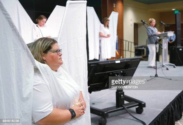 Jen Vargas stands with other volunteers of the 'Angels Force' group during the invocation by Reverend Terri Steed at a memorial service on the first...