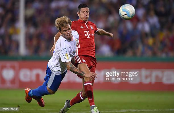 Jena's defender Rene Klingbeil and Bayern Munich's Polish striker Robert Lewandowski vie for the ball during the German Cup first round football...