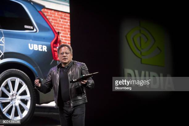 JenHsun Huang president and chief executive officer of Nvidia Corp holds a Nvidia Drive Pegasus RoboTaxi AI computer as he speaks during an event at...