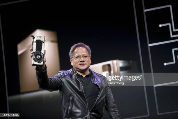 JenHsun Huang president and chief executive officer of Nvidia Corp holds a Nvidia Titan V supercomputer made for developers as he speaks during an...