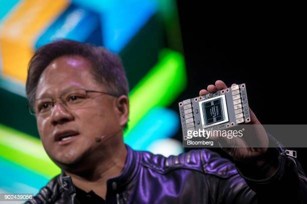JenHsun Huang president and chief executive officer of Nvidia Corp holds a Nvidia Volta 125 Teraflops per second Tensor Core as he speaks during an...